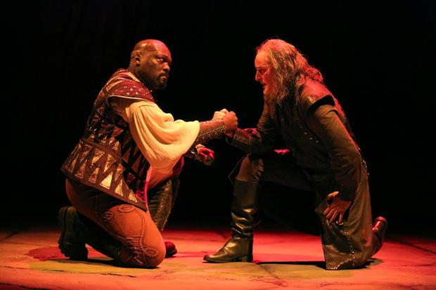 "Othello (Peter Macon) and Iago (Stephen Yoakam) plot Desdemona's murder amidst Michael Wangen's ""evil"" lighting. Photo credit: Joan Marcus."